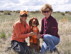 Vizsla Suede celebrates her NEW AKC Senior Hunter title with breeder/owner Judy Hetkowski and co-owner Mel